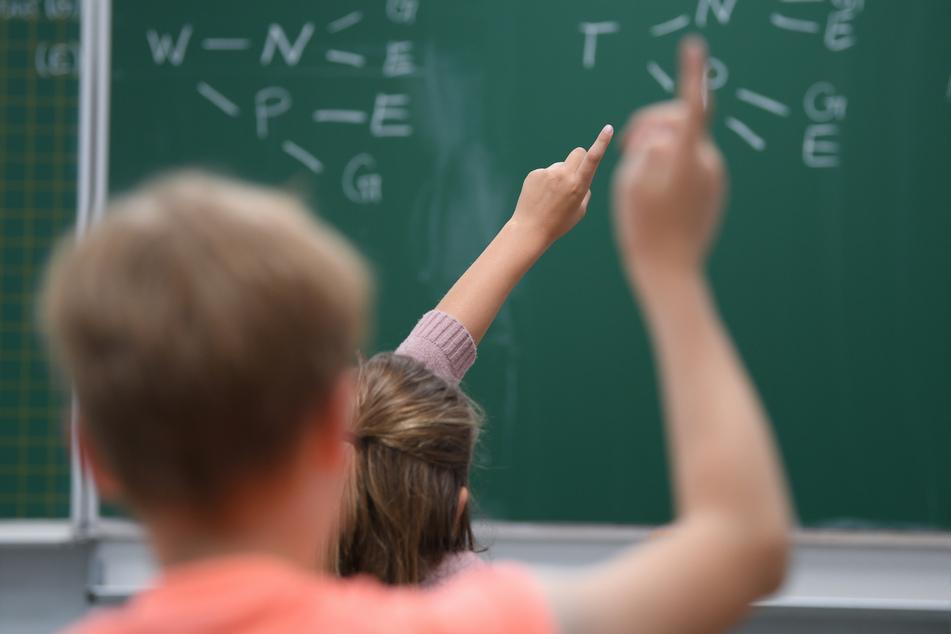 Schüler einer hessischen Grundschule melden sich im Unterricht (Symbolbild).
