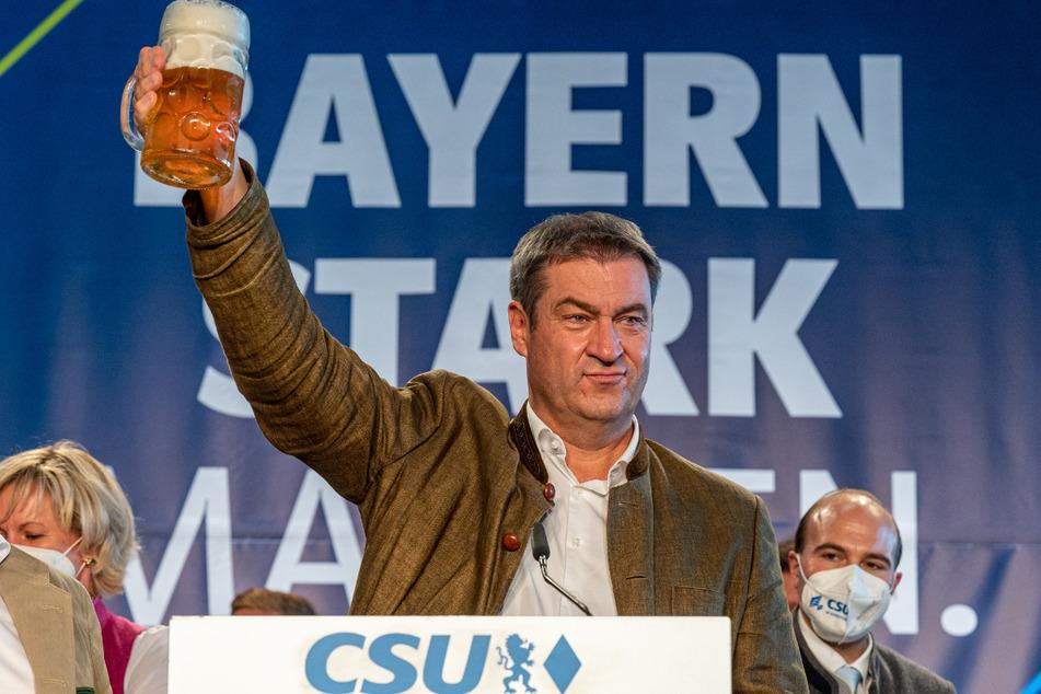 Bayerns Ministerpräsident Markus Söder (CSU) steht beim Politischen Frühschoppen Gillamoos mit einer Maß Bier auf der Bühne.