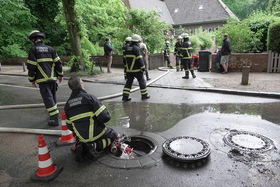 Feuerwehrleute pumpen Wasser aus der Einfahrt und dem Keller eines Hauses.