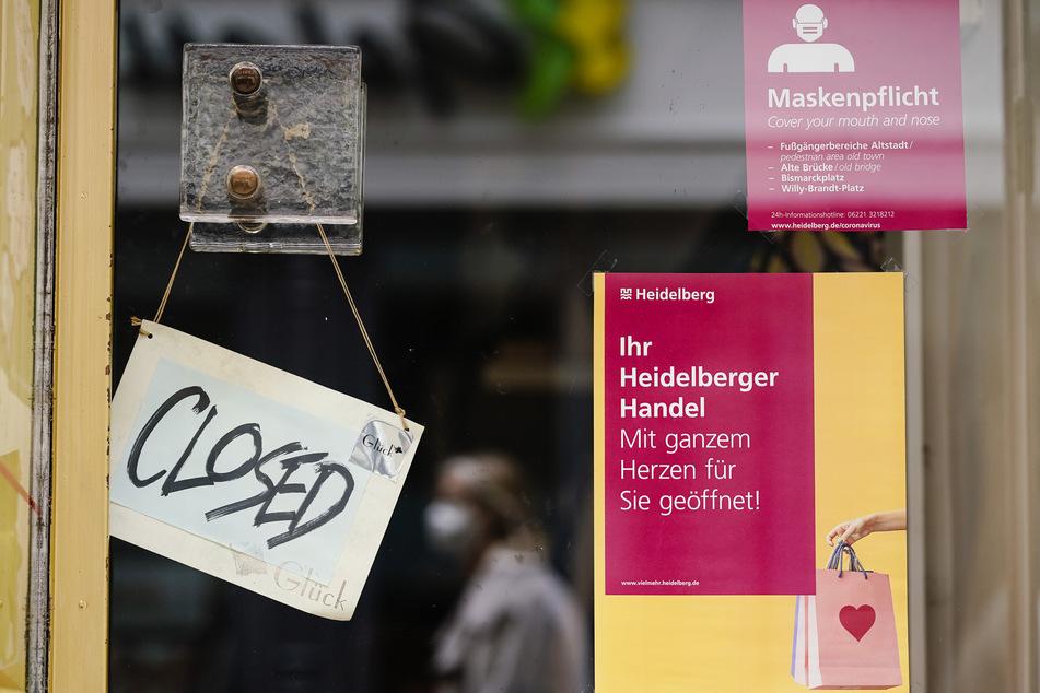 """Ein Schild mit der englischen Aufschrift """"Closed"""" hängt an der Tür eines Geschäfts in der Hauptstraße, einer Fußgängerzone und Einkaufsstraße in der Heidelberger Innenstadt."""