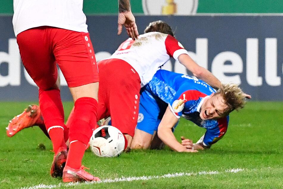 """Kiels Finn Porath (24, r.) fiel schon vor dem ersten Kontakt mit RWE-Sechser Marco Grote (34, M.). Den """"Skandal""""-Elfmeter gab es dennoch."""