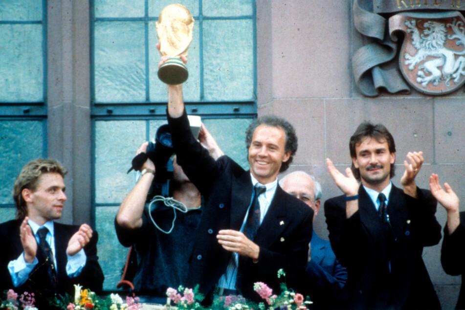 """""""Geht's raus und spielt Fußball!"""" Das sagte Franz Beckenbauer vorm WM-Finale 1990 in Rom gegen Argentinien seinen Kickern. Die taten genau das und holten den WM-Pokal, den Teamchef Beckenbauer hier in die Luft reckt."""
