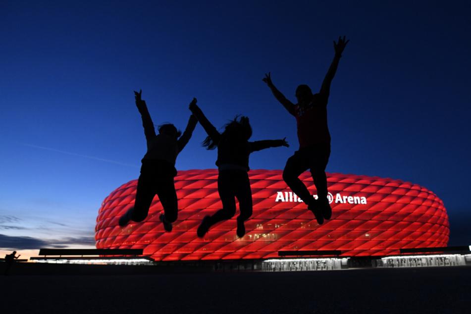 Drei Fans springen nach der Partie in der Fußball Bundesliga FC Bayern München - Borussia Mönchengladbach vor der Allianz Arena in die Höhe.