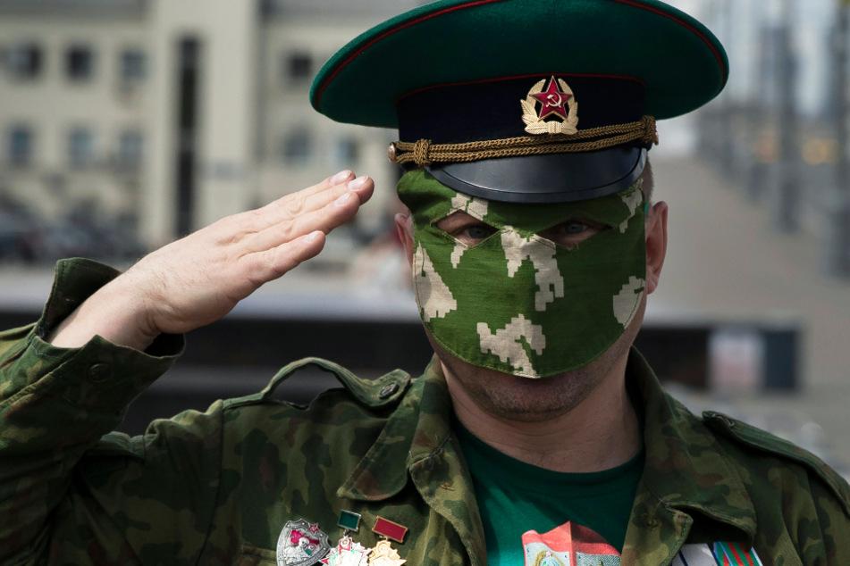 """Moskau: Ein ehemaliger russischer Grenzwächter, der zum Schutz vor dem Coronavirus eine Gesichtsmaske trägt, salutiert. Gemeinsam mit seinen Kameraden feiert er vor dem geschlossenen Vergnügungspark """"Gorki-Park"""" den Tag des Grenzsoldaten."""