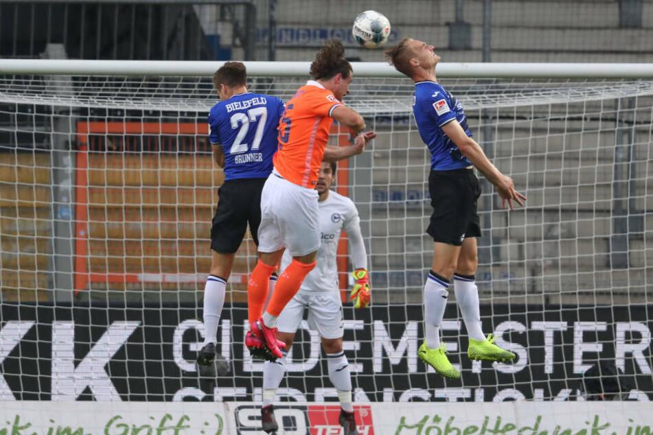 Bielefelds Cedric Brunner (l) und Amos Pieper (r) im Kampf um den Ball mit Yannick Stark (M).