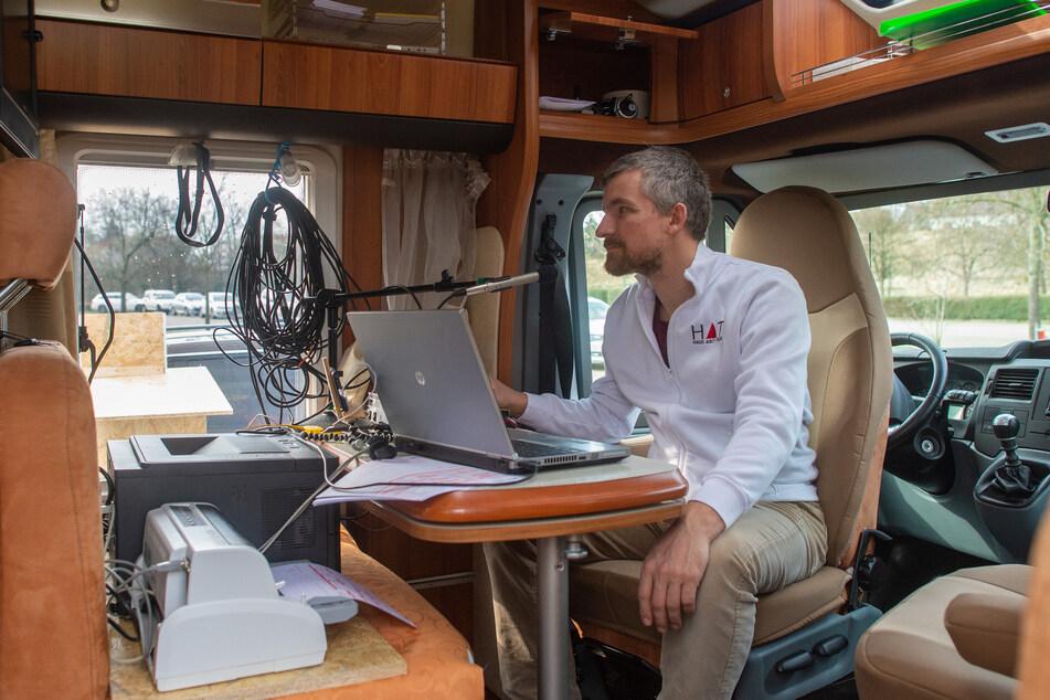"""Der Arzt Robin John sitzt in einem Wohnmobil und spricht über eine Sprechanlage mit Besuchern des """"Corona-Drive-in"""", während durch das Wohnmobilfenster eine Autoschlange mit weiteren Besuchern zu sehen ist."""