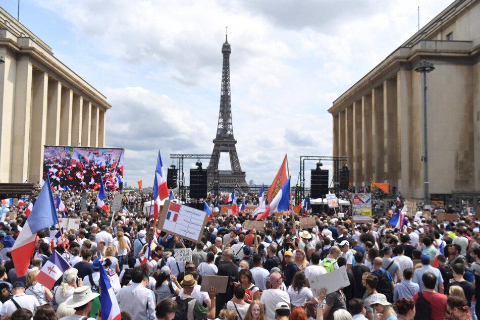 24.07.2021, Frankreich, Paris: Demonstranten nehmen auf der «Droits de l'homme»-Esplanade am Trocadero-Platz an einem Protest gegen die Impfpflicht für bestimmte Arbeitszweige und den von der Regierung geforderten obligatorischen Impfass teil. Foto: Alain Jocard/AFP/dpa +++ dpa-Bildfunk +++