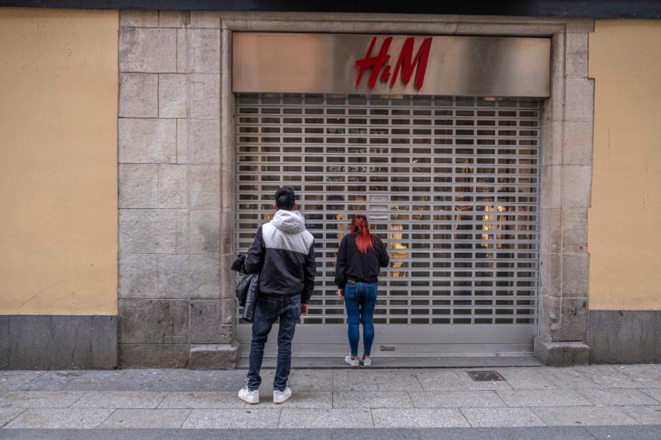 Spanien, Barcelona: Passanten stehen vor einer geschlossenen H&M-Filiale im Einkaufsviertel Portal del l'Angel.
