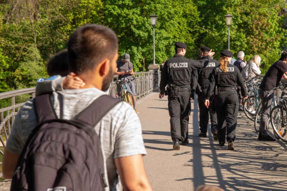 Polizisten gehen über die Kabelstegbrücke und schauen auf die von Sonnenanbetern belagerten Kiesbänke inmitten der Isar, die durch die bayerische Landeshauptstadt fließt.