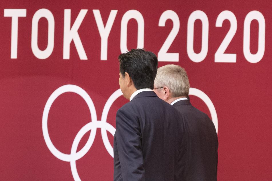 """Der Präsident des Internationalen Olympischen Komitees (IOC), Thomas Bach (re.), und der japanische Premierminister Shinzo Abe nehmen an der """"One Year to Go""""-Zeremonie für die Olympischen Spiele 2020 in Tokio teil. Wegen der Corona-Pandemie finden die Olympischen Spiele in diesem Jahr nicht statt."""