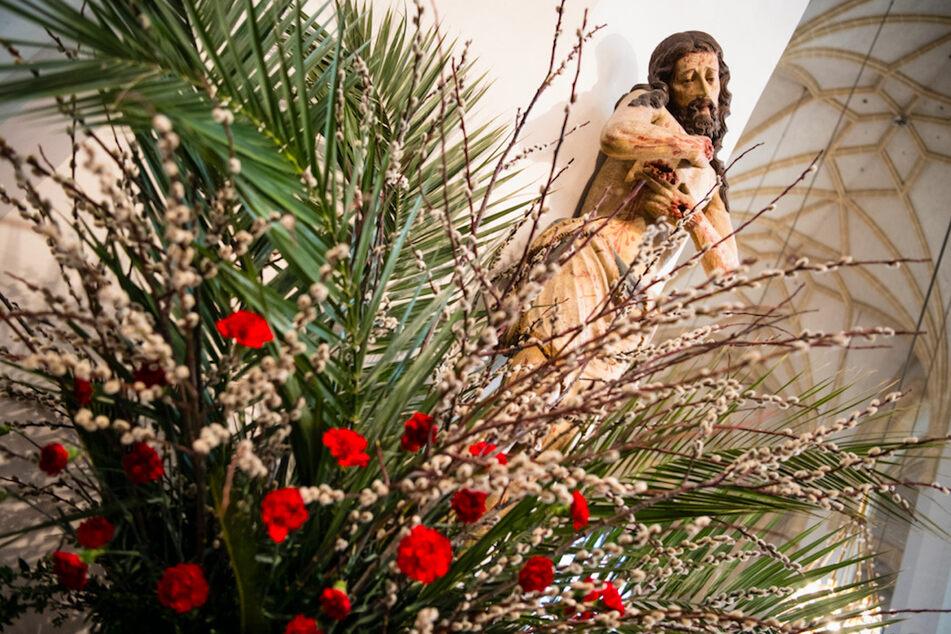 Eine Jesusfigur ist beim Palmsonntags-Gottesdienst hinter einem Gesteck aus Palmwedeln und Weidenkätzchen in der Frauenkirche in München zu sehen.