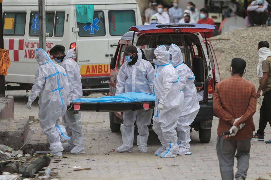 Mitarbeiter des Gesundheitswesens und Angehörige tragen den Leichnam einer Person, die an Covid-19 gestorben ist, zur Einäscherung.