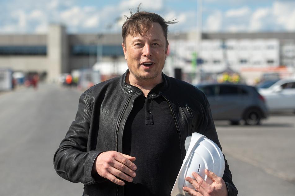 Tesla-Chef Elon Musk (49) steht auf der Baustelle der Tesla-Fabrik und hält seinen Schutzhelm im Arm.
