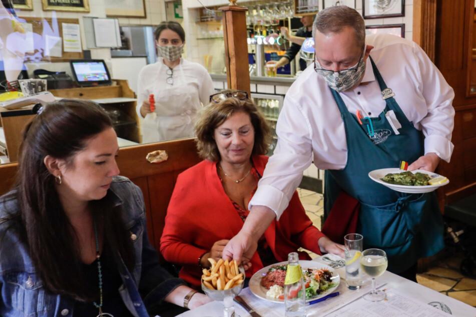 Belgien, Brüssel: Ein Kellner bringt Gästen im Restaurant Chez Léon ihr Essen an den Tisch.