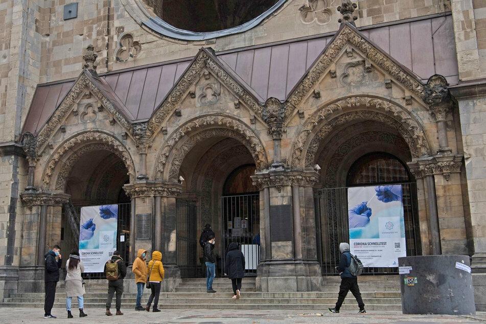 Menschen stehen in einer Schlange vor dem Eingang zur Gedenkhalle der Kaiser-Wilhelm-Gedächtnis-Kirche am Breitscheidplatz.