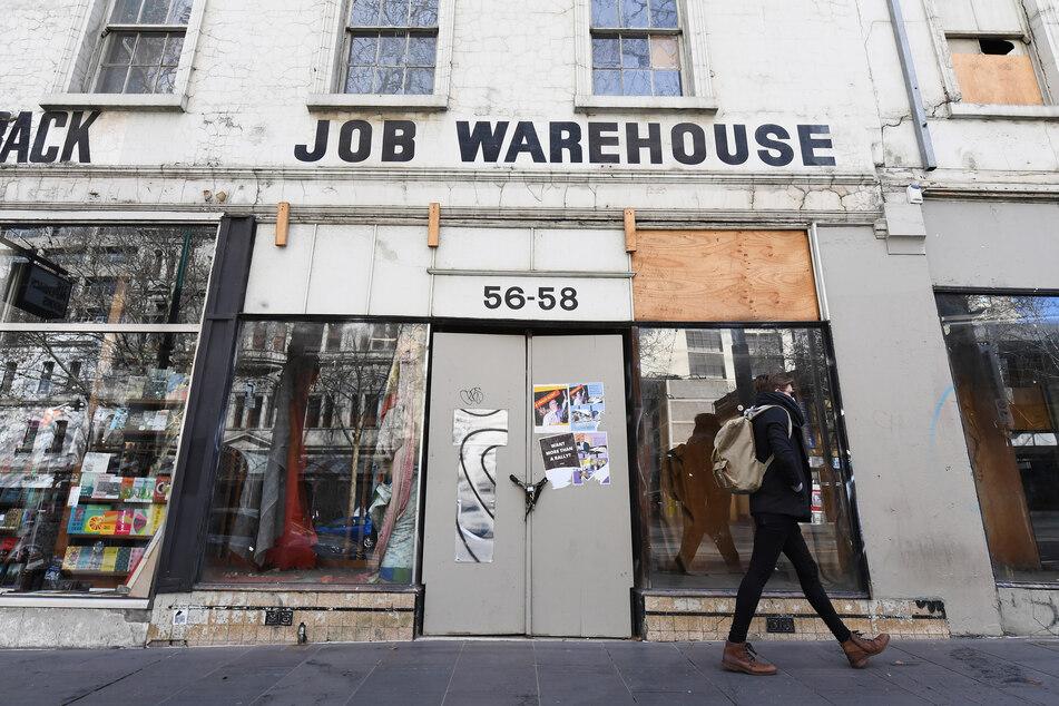 Eine Passantin geht in Melbourne an einem geschlossenen Geschäft vorbei.