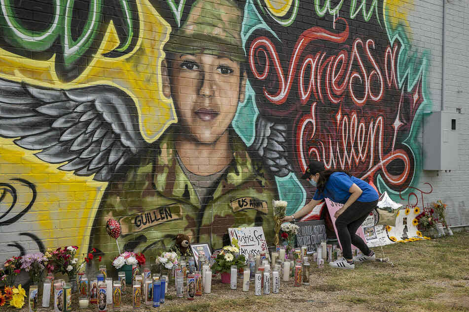 Mourners leave flowers and candles by a mural of Fort Hood Spc. Vanessa Guillén outside a convenience store in Austin.