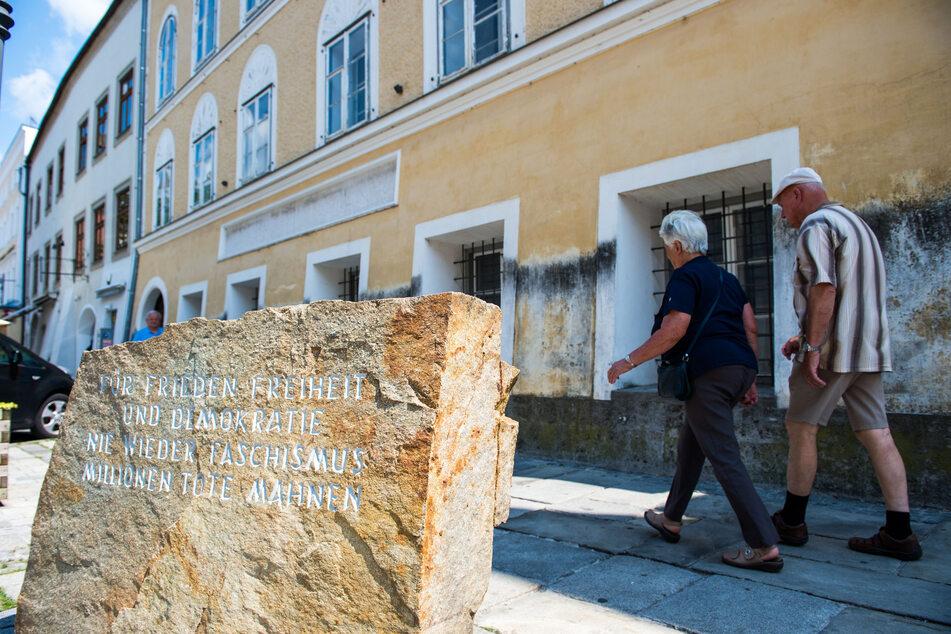 """Der Gedenkstein mit der mahnenden Aufschrift """"Für Frieden, Freiheit und Demokratie. Nie wieder Faschismus, Millionen Tote Mahnen"""" steht vor dem Geburtshaus von Adolf Hitler. (Archivbild)"""