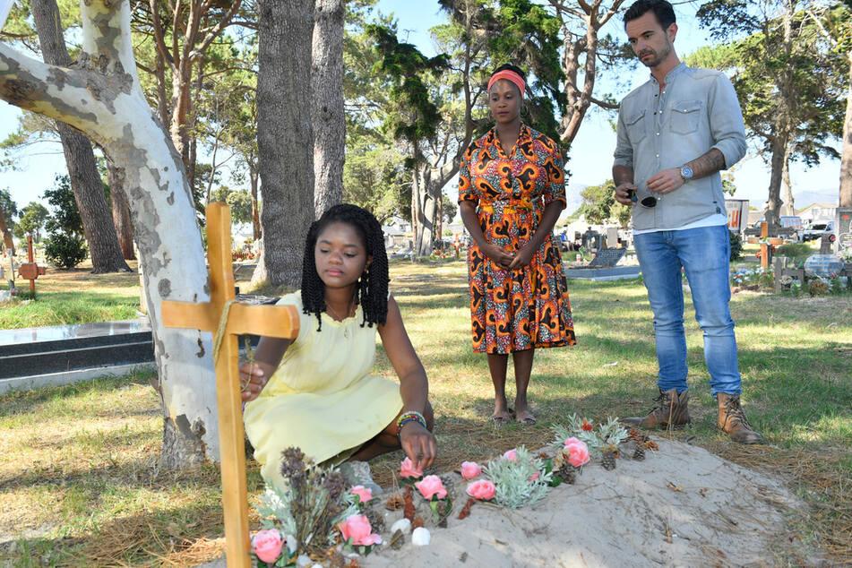 Kapitän Max Parger (Florian Silbereisen, r.) findet Lea (Melodie Wakivuamina, l.) nach langer Suche in Begleitung von Malaika Balewa (Motsi Mabuse, M.) auf einem Friedhof.
