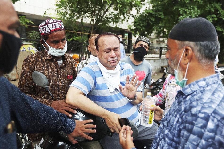 Angehörige von Patienten warten vor dem Shrey-Krankenhaus.