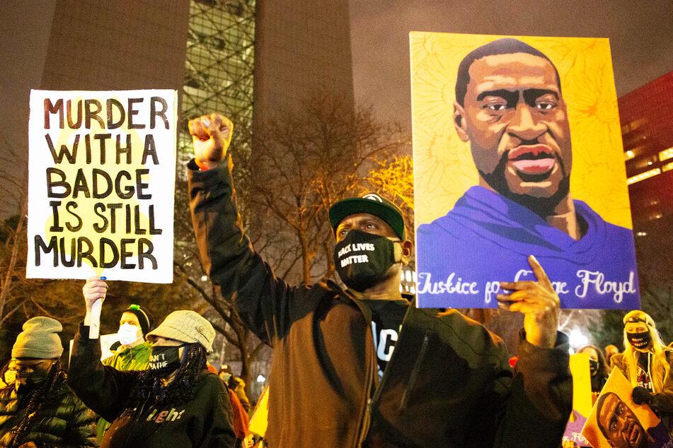 Ein Mann hält während einer Demonstration gegen Polizeigewalt ein Bild in die Höhe, das ein Porträt von George Floyd zeigt.