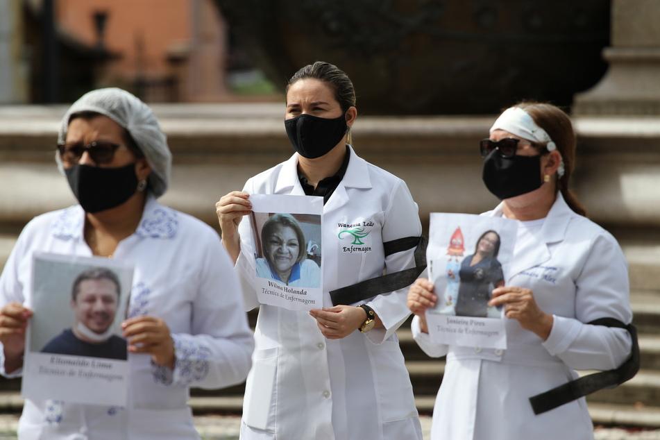 Mitglieder des Regionalrats der Krankenpfleger in Amazonas (COREN-AM) mit schwarzen Mundschutzmasken als Symbol der Trauer halten am internationalen Tag der Pflege Bilder von Kollegen hoch, die im Kampf gegen das Coronavirus gestorben sind.