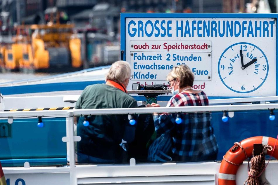 Passagiere sitzen auf dem Außendeck einer Barkasse.