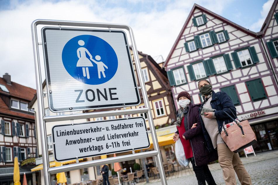 Zwei Frauen gehen mit Mund- und Nasenmasken durch die Innenstadt von Bad Urach.