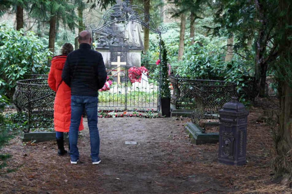 Besucher stehen vor dem Grab von Jan Fedder auf dem Ohlsdorfer Friedhof.