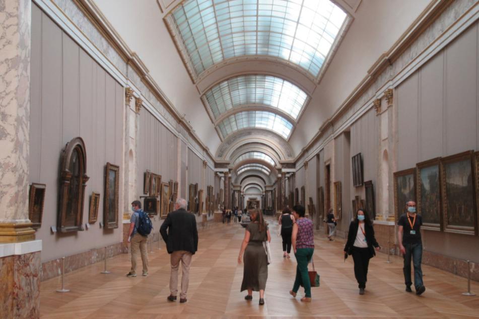 Mit Mundschutz gehen Besucher durch den Louvre.