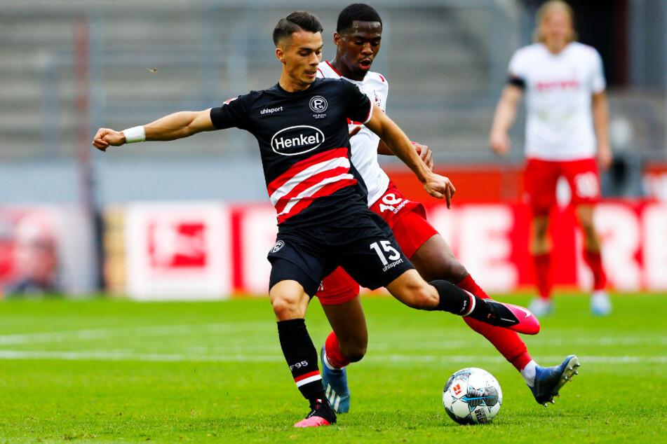 Düsseldorfs Torschütze zum 2:0, Erik Thommy (l.), wird von Kölns Kingsley Ehizibue attackiert.
