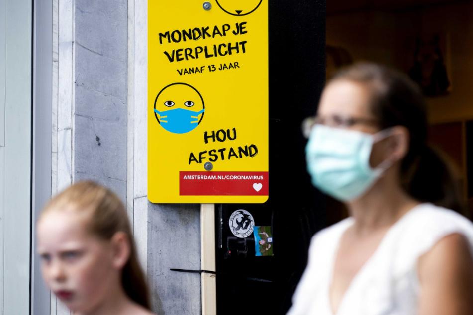 Amsterdam: Eine Frau mit Mundschutz geht an einem Schild mit Informationen über die Maskenpflicht vorbei.