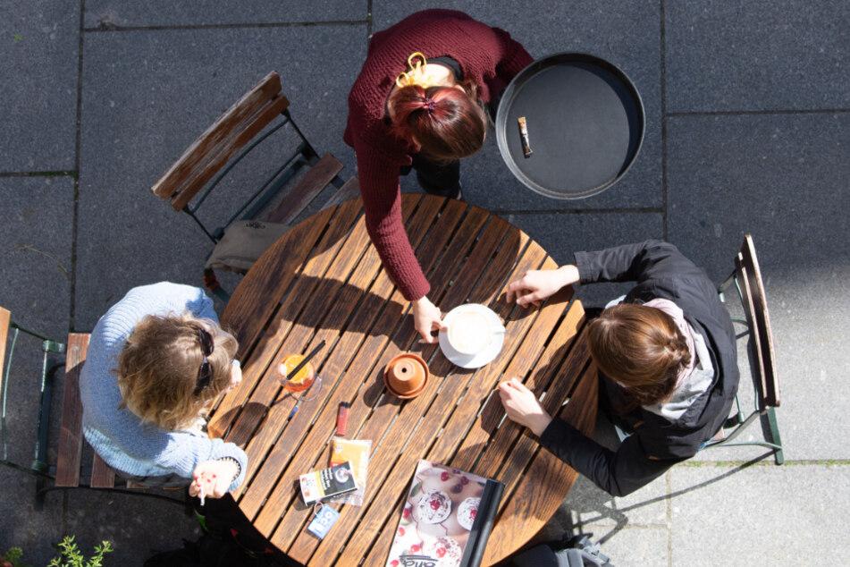 Zwei junge Frauen werden im Außenbereich eines Cafés von einer Kellnerin bedient.
