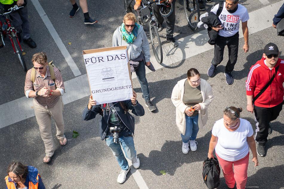 """Ein Mann hält während einer Demonstration der Initiative """"Querdenken 711"""" gegen die Corona-Maßnahmen ein Schild, auf dem """"Für das Grundgesetz"""" steht, hoch."""