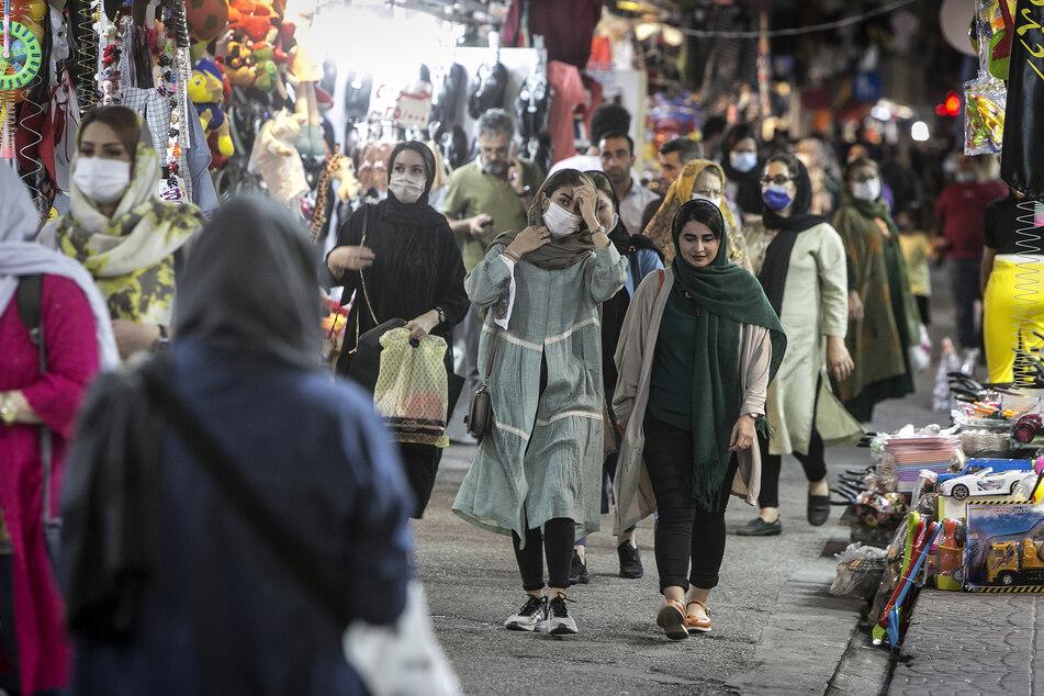 Besucherinnen tragen Mund-Nasen-Bedeckungen und gehen über einen Basar.