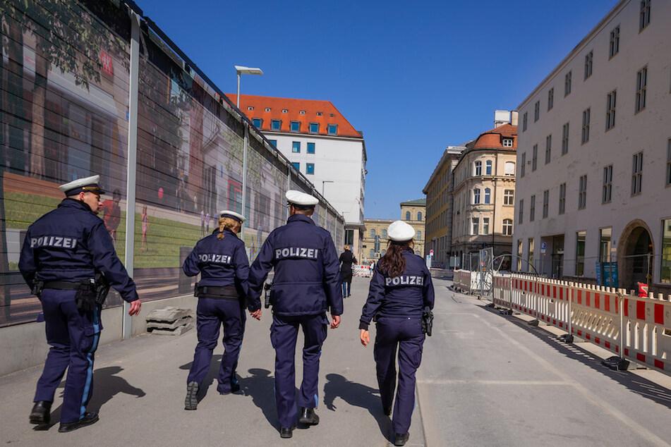 Vier Polizisten patroullieren durch eine fast leere Straße in der Innenstadt, hinter dem Münchner Rathaus.