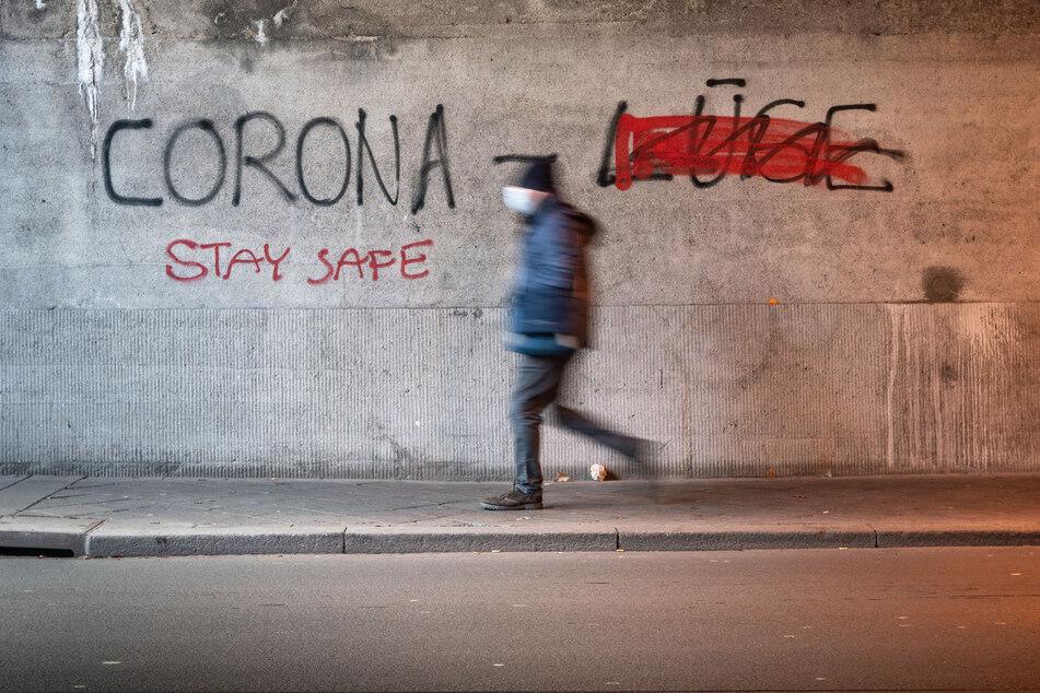"""An einer Wand steht """"Corona Lüge"""", wobei das Wort """"Lüge"""" (r.) durchgestrichen wurde. Weil viele Menschen in Zeiten der Pandemie verunsichert sind, hat die Landesberatungsstelle in Essen zahlreiche Anfragen zu Verschwörungstheorien erhalten."""