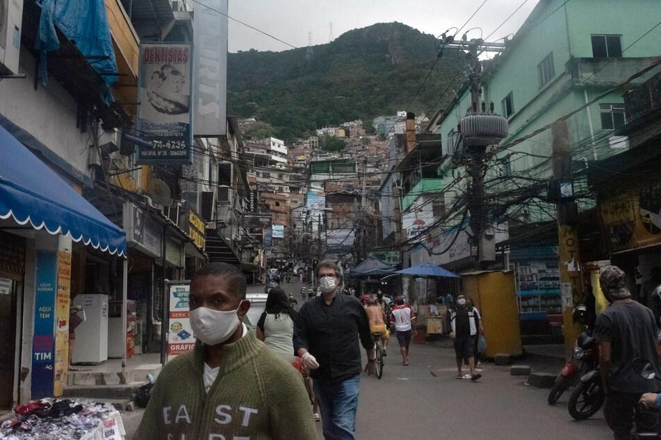 """Menschen gehen mit Mundschutz durch eine Straße der Favela """"Rocinha"""". In Brasilien sind über 28.000 Patienten im Zusammenhang mit der Lungenkrankheit Covid-19 gestorben."""