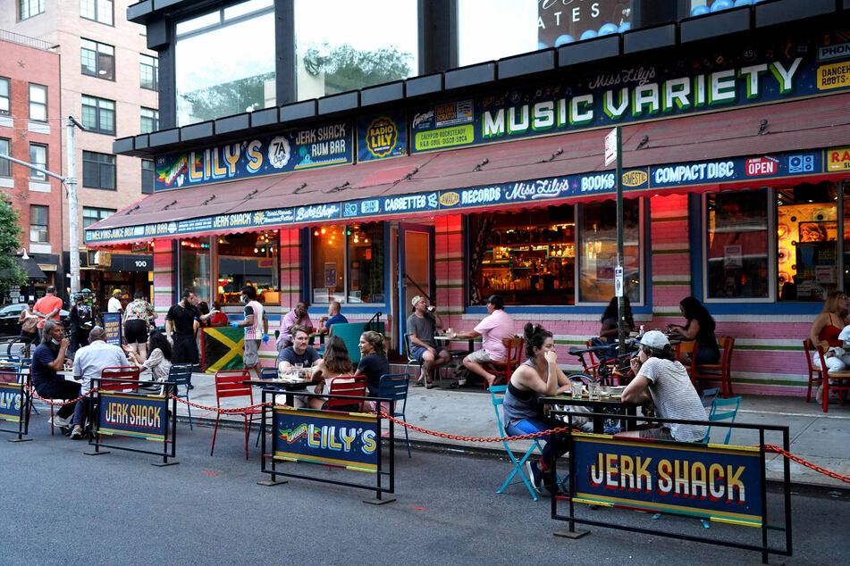"""Gäste des Restaurants """"Miss Lily's"""" sitzen an Tischen vor der Gaststätte in Lower Manhattan in New York."""