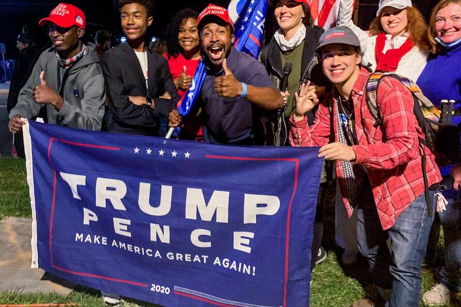 Eine Gruppe von Anhängern von US-Präsident Donald Trump, steht mit einer Trump-Fahne gegenüber dem Eingang zum Walter-Reed-Militärkrankenhaus.