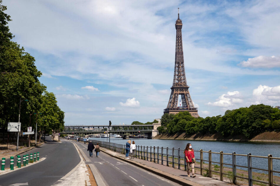 Frankreich, Paris: Menschen spazieren an der Seine neben dem Eiffelturm.
