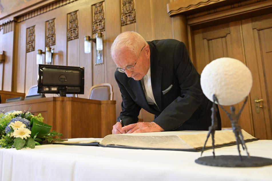 """Hartwig Albiro (89) trägt sich in das Goldene Buch der Stadt ein. Die Bronze-Skulptur """"Gemeinsam sind wir stark"""" gab es für die AG dazu."""