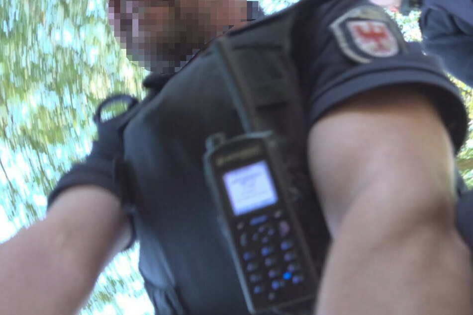 Ein Screenshot aus dem Video zeigt, wie der Fotograf von dem Polizeibeamten zu Boden gedrückt und gewürgt wird.