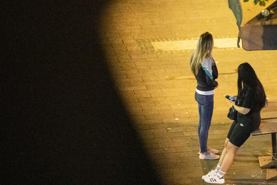 Zwei junge Prostituierte aus Osteuropa warten im Schein einer Laterne auf der Kaiserstraße im Bahnhofsviertel von Frankfurt auf Kunden.