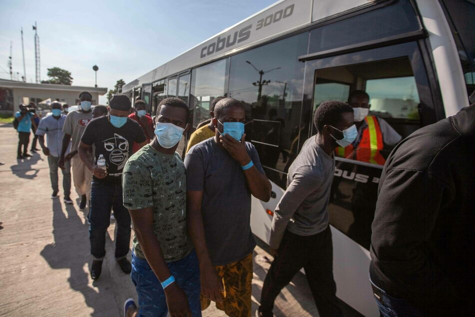 Haitian migrants get off a bus after being deported from the United States.