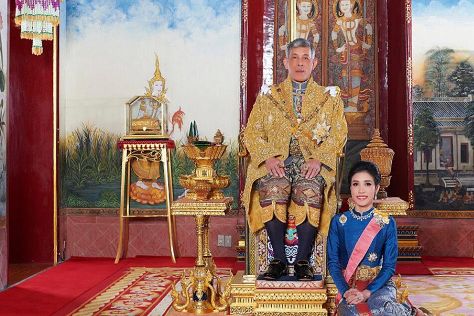 König Maha Vajiralongkorn von Thailand (68) sitz auf seinem Thron, während neben ihm Sineenat Wongvajirapakdi (35) kniet. Die zuvor Verstoßene wurde nun begnadigt.
