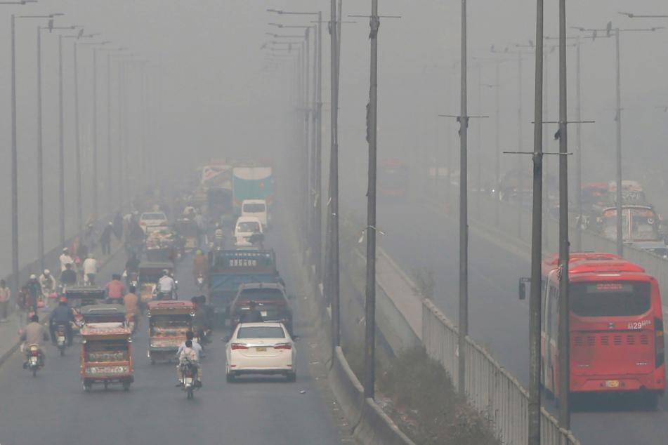 Lahore, Pakistan: Fahrzeuge fahren auf einer Autobahn, während Smog das Gebiet einhüllt.