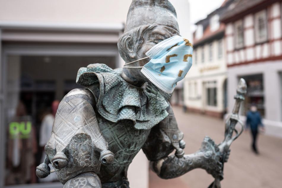 Die Figur des Bajazz auf dem Fastnachtsbrunnen in der fast menschenleeren Fußgängerzone von Dieburg trägt eine Mund-Nasen-Bedeckung.