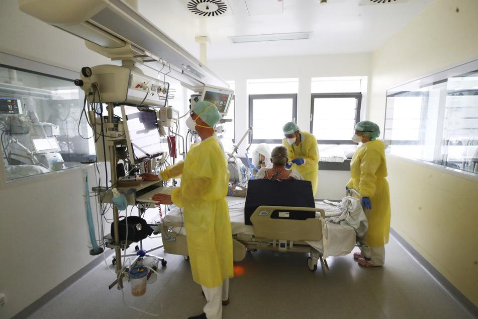 Ärzte und Pfleger untersuchen einen Patienten auf einer Covid-19-Intensivstation in Thüringen. Im Freistaat bleibt die Zahl der täglichen Neuinfektionen auf hohem Niveau.