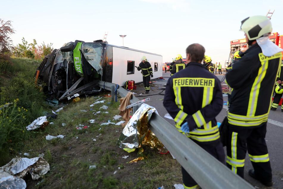 Feuerwehrleute stehen neben dem verunglückten Flixbus, in dem eine Insassin aus Italien starb. (Archiv)